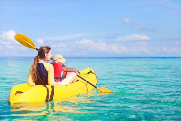 Mother and son kayaking at tropical ocean